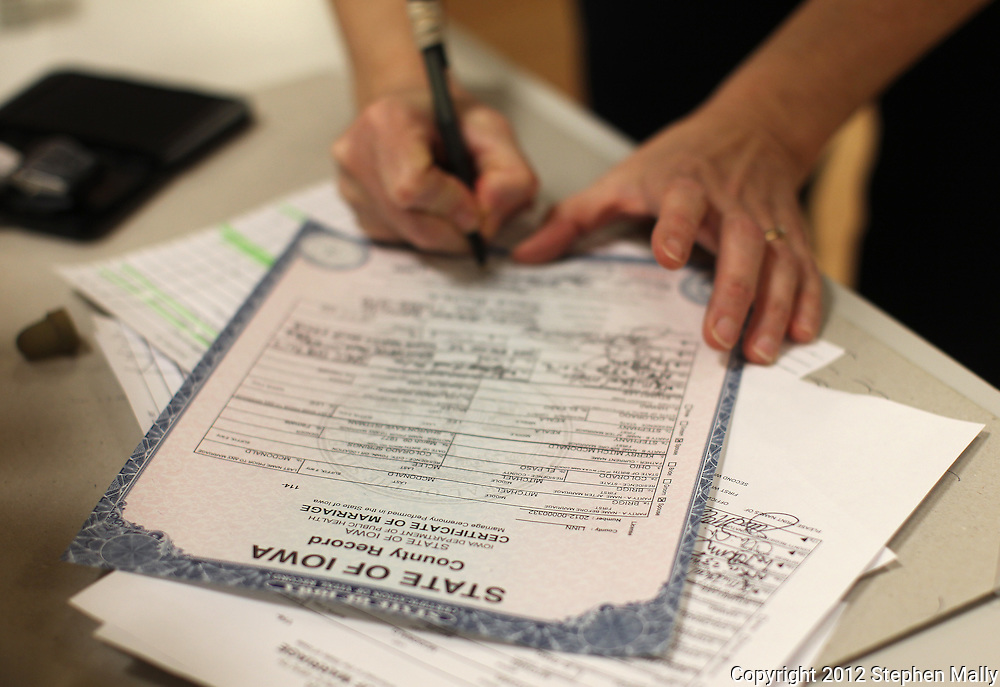 Linn County clerk Mary Hall works on the certificate of marriage for Stephany Lee and Brigg McDonald at Linn County West in Cedar Rapids on Monday, April 23, 2012.