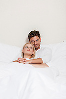 Portrait of happy young man with woman relaxing in bed