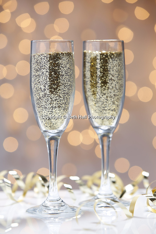 Stock photography of glitter filled champaign glasses with holiday lights. Photo by Beth Hall