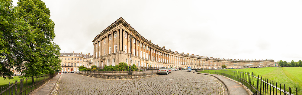 A high resolution panorama of Royal Crescent, an historic row of well-to-do houses in Bath, Somerset, United Kingdom. The Royal Crescent is a street of 30 terraced houses laid out in a sweeping crescent in the city of Bath, England. Designed by the architect John Wood the Younger and built between 1767 and 1774, it is among the greatest examples of Georgian architecture to be found in the United Kingdom and is a Grade I listed building. Although some changes have been made to the various interiors over the years, the Georgian stone façade remains much as it was when it was first built.