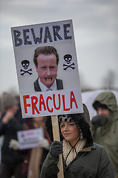 "© Licensed to London News Pictures . 26/01/2014 . Salford , UK . A woman holds a placard with "" Beware Fracula "" around a photograph of Prime Minister David Cameron . Approximately 500 protesters march to an iGas fracking exploration site at Barton Moss , Salford , today (Sunday 26th January 2014) . They walk along the A57 road , blocking traffic as they do . A long term protest camp has been established on an access road leading to the site and today (26th January) protesters from other areas of the country travelled to the site to join with other protesters against fracking . Photo credit : Joel Goodman/LNP"