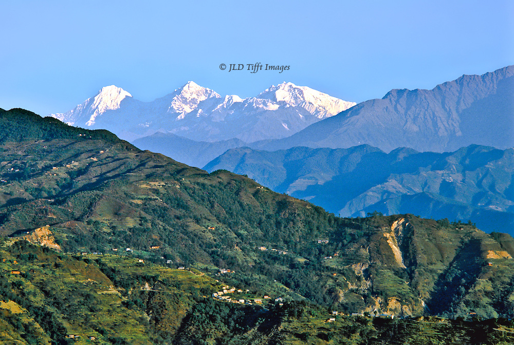 landscape with Langtang Himal in the distance over rolling foothills, seen from Nagarkot, Kathmandu Valley, Nepal.