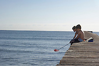 Two boys (6-11) sitting on jetty with fishing net