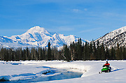 Alaska. Petersville. Mt McKinley (20,320 ft) and snowmachiners.