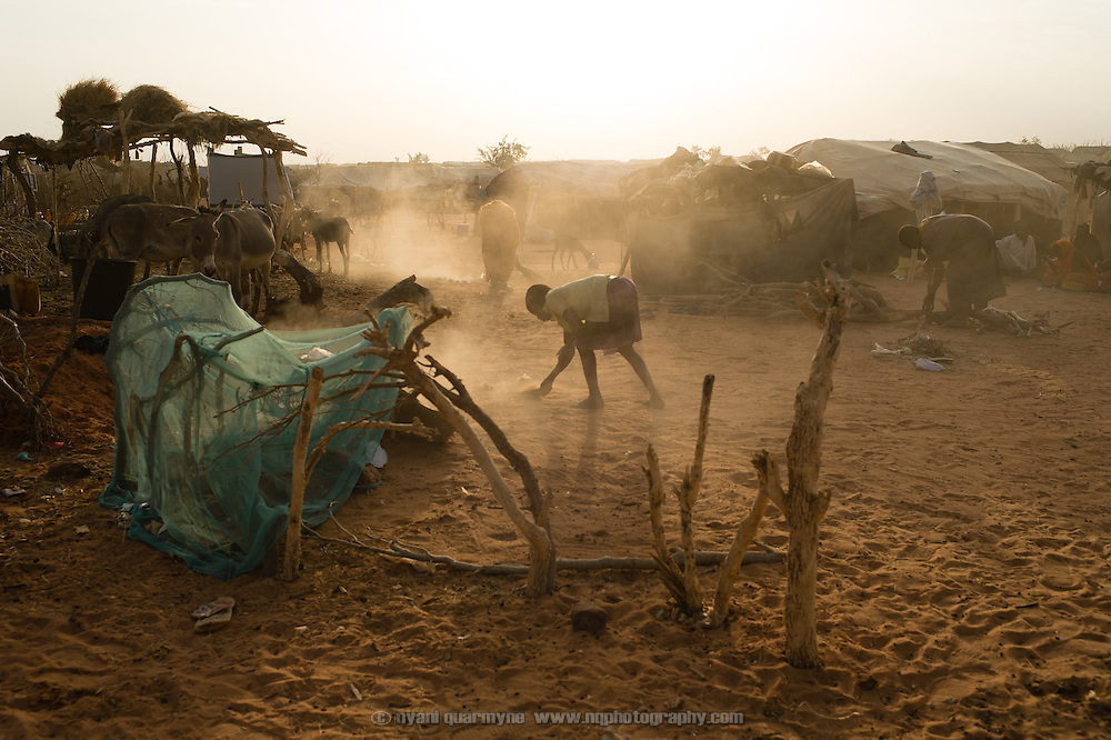A girl and her mother sweep the area around their tent at the Mbera camp for Malian refugees in Mauritania on 3 March 2013.