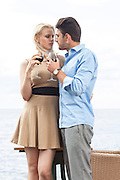 Romantic young couple holding red wine glass at outdoor restaurant by lake