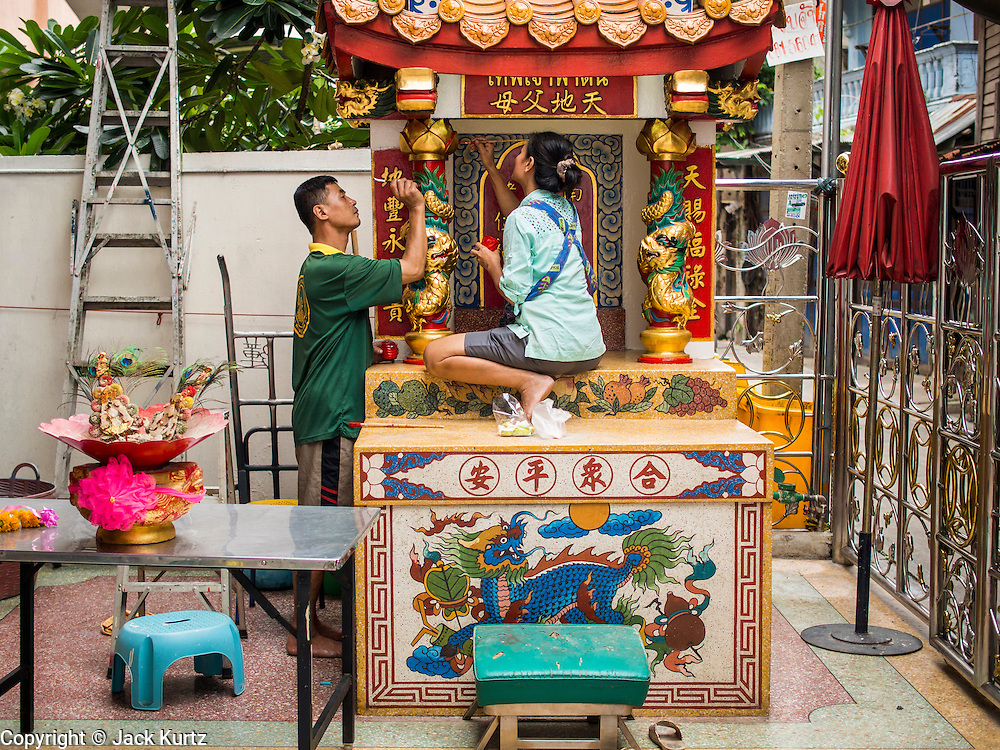 14 AUGUST 2014 - BANGKOK, THAILAND:     A man and woman paint a small Chinese shrine in the Talat Noi section of Bangkok. Most Thais are Theravada Buddhists but many Chinese-Thais are Mahayana Buddhists. Talat Noi is a small part of Chinatown that dates back to the Ayutthaya period. It is a melting pot of various cultures and was originally settled by Portuguese,  Vietnamese, Hokkien, Teochew and Hakka Chinese. Now it is mostly small mechanical shops and used car parts.   PHOTO BY JACK KURTZ