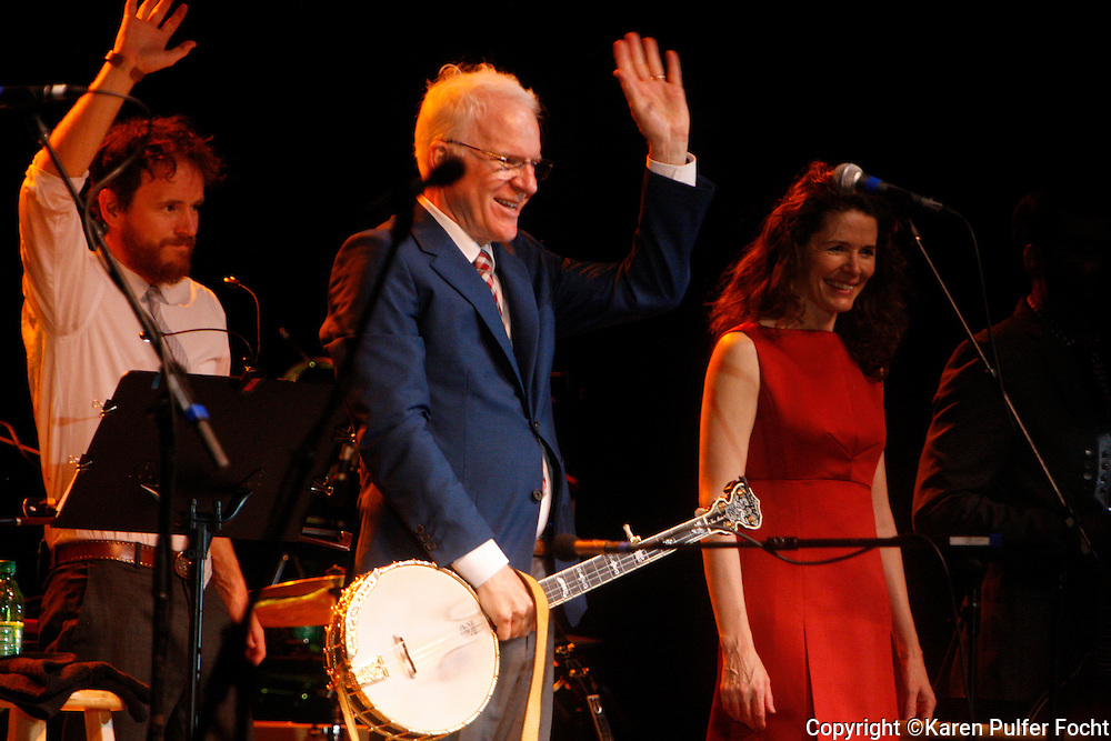 """August 2, 2013 - Comedian Steve Martin, performed at Snowden Grove Amphitheater, Saturday evening, in his more current role as a blue grass musician as he wound up his tour. He is touring with the North Carolina bluegrass band the Steep Canyon Rangers and singer-musician Edie Brickell (right). He did use every opportunity to still get a laugh, while performing with his banjo. The Martin-Brickell the pair has collaborated on a musical together. """"Bright Star,"""" based on an original story by the two set in the Blue Ridge Mountains in the early 20th century, will have its world premiere September 13 at the Old Globe Theater in San Diego, California."""