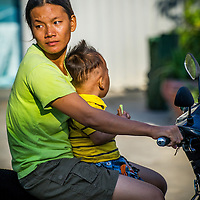 Jan 4, 2013 - A mother holds onto her child whild riding in the Cambodian capital city of Phnom Penh.<br /> <br /> Story Summary: Amidst the feverish pace of Phnom Penh&rsquo; city streets, a workhorse of transportation for people and goods emerges: Bicycles, motorcycles, scooters, Mopeds, motodups and Tuk Tuks roam in place of cars and trucks. Almost 90 percent of the vehicles roaming the Cambodian capital of almost 2.3 million people choose these for getting about. Congestion and environment both benefit from the small size and small engines. Business is booming in the movement of goods and and another one million annual tourists in Cambodia&rsquo;s moto culture.