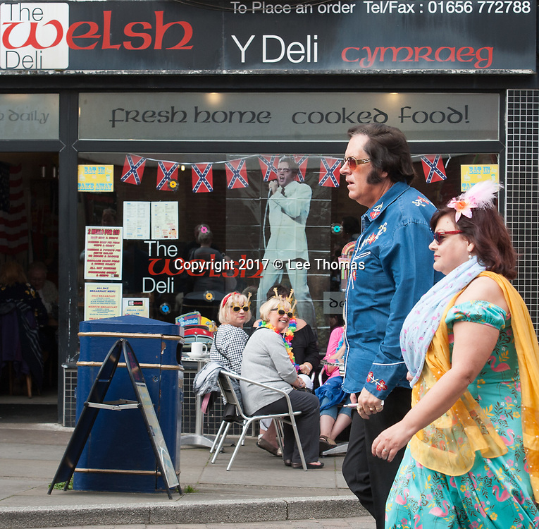 Porthcawl, County Borough of Bridgend, Wales, UK. 23rd September 2017. Pictured:  Elvis fans walk past a Welsh Deli in Porthcawl's main shopping street. /  In the 40th year since his death, thousands of Elvis fans descend on the Welsh seaside town of Porthcawl for a celebration of The King. Taking place over the weekend the event consists of hundreds of shows across 20+ venues. The main event The Elvies is, according to organisers, the world's leading award show for Elvis tribute artists and is held in the magnificent Grand Pavilion. // Lee Thomas, Tel. 07784142973. Email: leepthomas@gmail.com  www.leept.co.uk (0000635435)