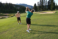 Man tees off on the Whistler Golf Course, located in the mountains of Whistler, BC Canada.
