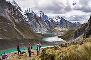 Quesillococha (a green lake at 4332 m), Lake Siula, and Lake Gangrajanca lie at the feet of massive peaks in the Cordillera Huayhuash in the Andes Mountains, Huaraz, Peru, South America. This photo is at viewpoint halfway up the pass of Siula Punta.  Day 3 of 9 days trekking around the Cordillera Huayhuash. Published in Wilderness Travel Catalog 2019.