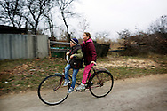 Arkadiy and Angelina Yatsenko, 8 and 11 ride a bicycle at a road next to their house. They live with their uncle and mother who is unemployed, surviving just from what the land offers them and from state fares. The children have to walk several kilometers to get to school every day.