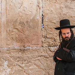 Orthodox Jew with his Thora standing in front of the Western wall, Jerusalem, Israel.