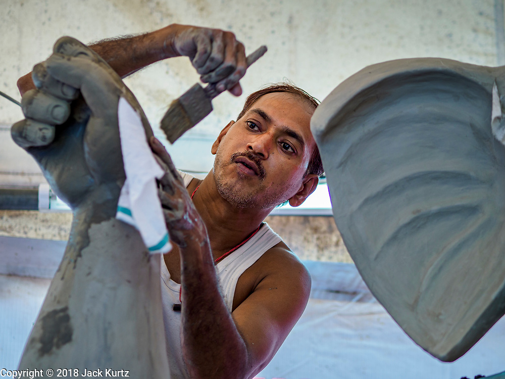 08 SETEMBER 2018 - BANGKOK, THAILAND:  A craftsman applies sealant to the unpainted clay on a Ganesh statue at Wat Witsanu Hindu Temple, also called the Vishnu Temple, in Bangkok. Indian craftsmen are making statues of the Hindu deity Ganesha for the Ganesh Chaturthi, or Ganesh Festival, held at Hindu temples in September. All of the craftsmen, and the clay they use to fashion the statues, come from India every year to make the statues. Although Thais are predominantly Buddhist, the Lord Ganesh, the Hindu overcomer of obstacles, is worshipped by many Thais and Ganesh Chaturthi is celebrated in many Thai communities.       PHOTO BY JACK KURTZ