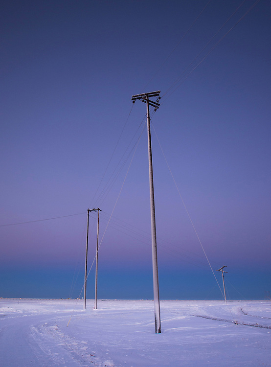 Powerlines form an interesting triangular compositon after sunset in Prudhoe Bay Alaska,