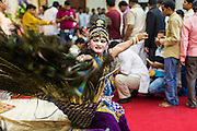 "17 AUGUST 2014 - BANGKOK, THAILAND:  A man dressed as a peacock, which represents the ""Vahana"" or a bearer of the gods, performs for Krishna Janmashtami in the Vishnu temple in Bangkok. Krishna Janmashtami is the annual celebration of the birth of the Hindu deity Krishna, the eighth avatar of the Hindu god Vishnu. It is celebrated by Hindus in Thailand. There are about 53,000 Hindus in Thailand, most originally from India, but many Hindu deities are highly revered by Thai Buddhists and Hindu holy days are observed by many Thai Buddhists.       PHOTO BY JACK KURTZ"