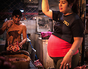 A butcher works at a butchers stall with his pregnant wife at the Huembes market in Managua, Nicaragua