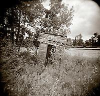 PL09009-00...MINNESOTA - Holga image of abandoned outhouse near a north woods pond.