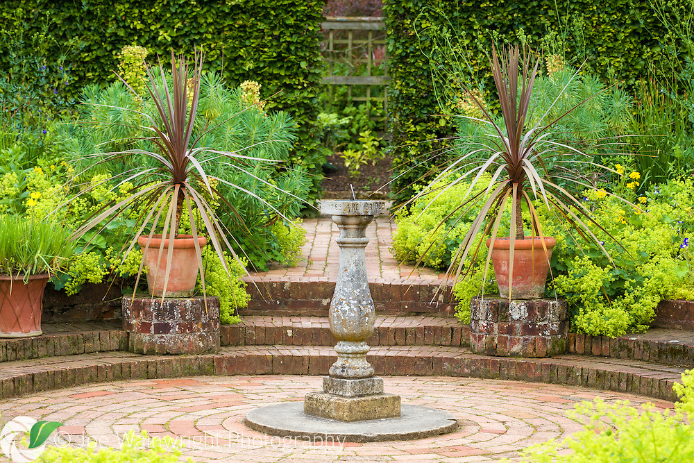 A sundial and bronze cordylines are key features of Mrs Winthrop's Garden at Hidcote Manor Garden, Gloucestershire.