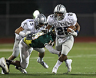 Xavier's Brendan Miller (25) tries to pull away from Kennedy's Anthony Carter (14) on a run during their game at Kingston Stadium in Cedar Rapids on Friday, September 27, 2013.
