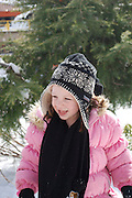 Smiling young girl of 5 in pinK clothes plays outdoors an a sunny winter day