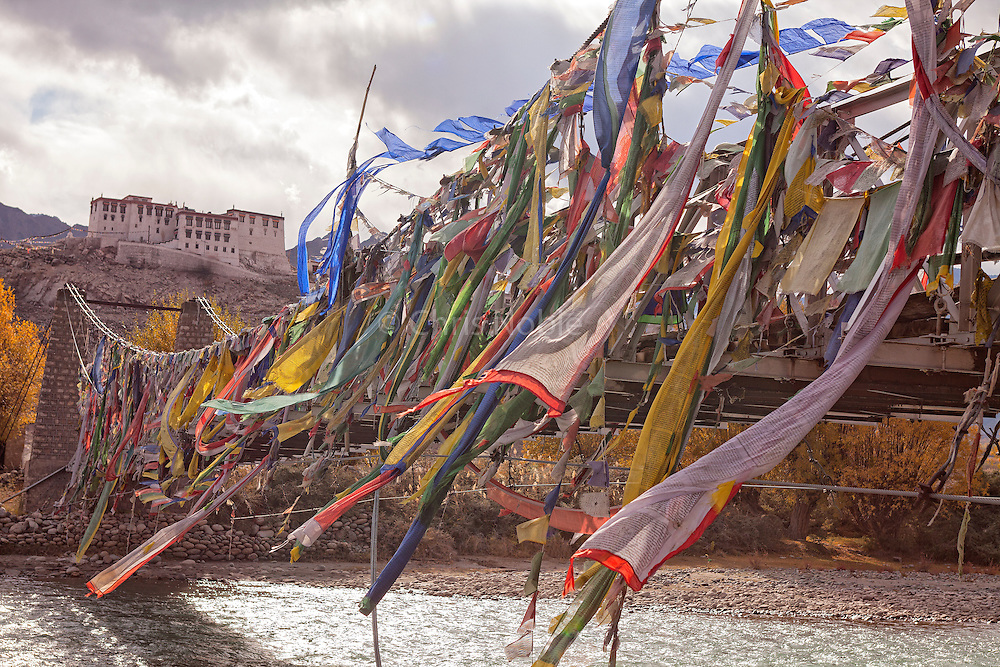 Prayer flags adorn the bridge crossing the Indus River to Stakna Monastery in Ladakh, India.