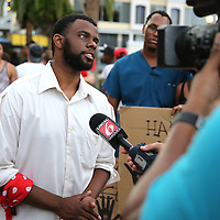 "DeQuan Shanks speaks with local media at Lake Eola park during the ""National Moment of Silence"" event at the Lake Eola bandshell in downtown Orlando, Florida on Thursday, August 14, 2014. In light of the recent killing of eighteen year old Mike Brown in Ferguson, Missouri, citizens across America are gathering in solidarity to hold vigils and observe a moment of silence to honor victims of suspected police brutality. (AP Photo/Alex Menendez)"