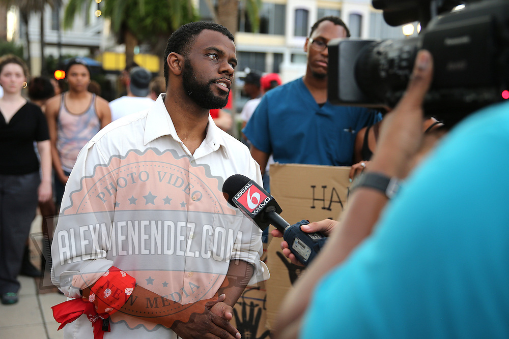 """DeQuan Shanks speaks with local media at Lake Eola park during the """"National Moment of Silence"""" event at the Lake Eola bandshell in downtown Orlando, Florida on Thursday, August 14, 2014. In light of the recent killing of eighteen year old Mike Brown in Ferguson, Missouri, citizens across America are gathering in solidarity to hold vigils and observe a moment of silence to honor victims of suspected police brutality. (AP Photo/Alex Menendez)"""