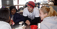 Joe Melendrez (center, red hat) talks to Cynthia Olorunsemi (left) as Dominque Wright (on Joe's left,) and Trish Graham (right) listen during a burrito party for the homeless hosted by U.D. Religious Studies student Joe Melendrez at Chipotle's on Brown Street in Dayton.