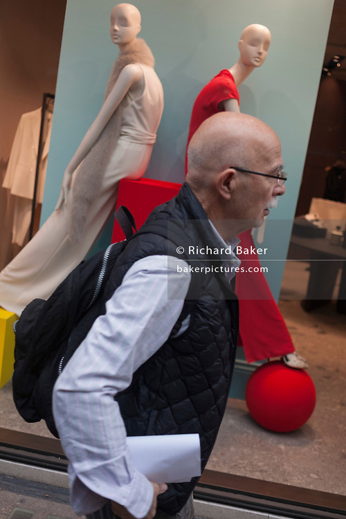 Bald mannequins in the background with a bald passer-by in Bond Street, on 15th December 2016, in London, England.