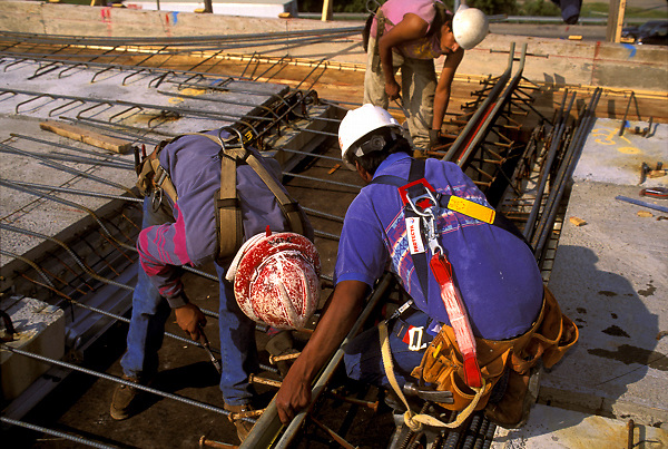 Stock photo of three men working with rebar at a construction site