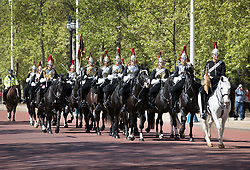 © Licensed to London News Pictures. 04/05/2018. London, UK. Tourists watch as members of The Household Cavalry Mounted Regiment make their way along The Mall in the sunshine in  central London. High temperatures are expected to continue throughout the bank holiday weekend. Photo credit: Peter Macdiarmid/LNP