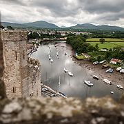 Boats moored on the river far below as seen from the top of one of the distinctive towers at Caernarfon Castle in northwest Wales. A castle originally stood on the site dating back to the late 11th century, but in the late 13th century King Edward I commissioned a new structure that stands to this day. It has distinctive towers and is one of the best preserved of the series of castles Edward I commissioned.
