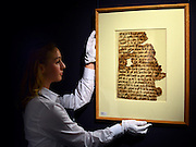 "© Licensed to London News Pictures. 28/09/2012. London, UK A member of auction room staff holds a rare Qur'an leaf in late Hijazi script from the late 7th-early 8th century. It is expected to raise 100,000-150,000GBP. Sotheby's Auction rooms in New Bond Street, London hold a photo call for their upcoming ""arts of the Islamic World"" auction which is expected to realise in the region of 5 million GBP . Photo credit : Stephen Simpson/LNP"