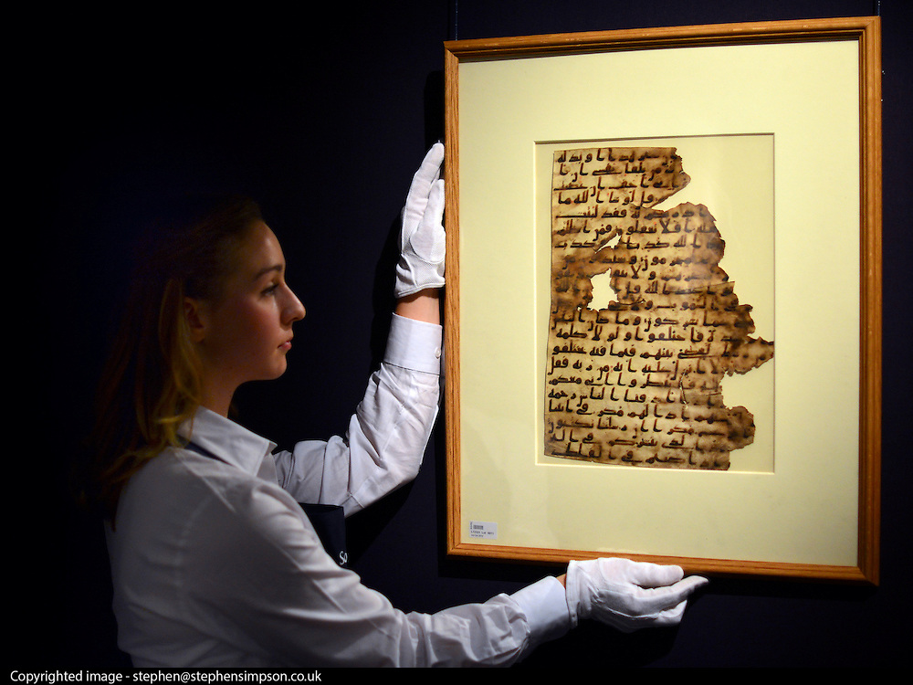 """© Licensed to London News Pictures. 28/09/2012. London, UK A member of auction room staff holds a rare Qur'an leaf in late Hijazi script from the late 7th-early 8th century. It is expected to raise 100,000-150,000GBP. Sotheby's Auction rooms in New Bond Street, London hold a photo call for their upcoming """"arts of the Islamic World"""" auction which is expected to realise in the region of 5 million GBP . Photo credit : Stephen Simpson/LNP"""