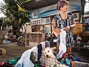 16 NOVEMBER 2015 - BANGKOK, THAILAND:  A woman being evicted from her home dries her dog after washing him in the Wat Kalayanamit neighborhood. Fifty-four homes around Wat Kalayanamit, a historic Buddhist temple on the Chao Phraya River in the Thonburi section of Bangkok, are being razed and the residents evicted to make way for new development at the temple. The abbot of the temple said he was evicting the residents, who have lived on the temple grounds for generations, because their homes are unsafe and because he wants to improve the temple grounds. The evictions are a part of a Bangkok trend, especially along the Chao Phraya River and BTS light rail lines. Low income people are being evicted from their long time homes to make way for urban renewal.          PHOTO BY JACK KURTZ