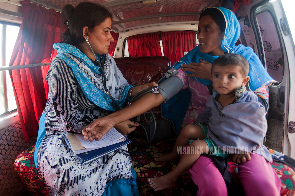 TANDO BAGO, PAKISTAN - OCTOBER 4: Flood-affected women receive medical evaluations and nutritional suppliments for their children at a roadside mobile nutrition centre, on October 4, 2011, in Tando Bago, Pakistan. Extreme poverty, poor diet and health, exposure to disease, and inadequate sanitation and hygiene annually produce alarming levels of malnutrition amongst children, but the floods of 2010 and 2011 have increasingly endangered an already vulnerable population. Child malnutrition has breached emergency levels in Pakistan - particularly Sindh province - after monsoon floods devastated the country's poorest region for a second year. Malnourishment It is the single biggest contributor to under-five mortality, increasing the risk of infections and slowing recovery from illness. It stuns both mental and physical growth and their future capacity, sapping the next generation's ability to meet the demands of a country already facing an unstable future. According to UN reports, hundreds of thousands of children in Pakistan suffer from severe-acute-malnutrition, with 15.1% of children experiencing acute malnourishment. The Economist recently reported that 44% of children in Pakistan suffer from varying degrees of malnutrition. (Photo by Warrick Page)