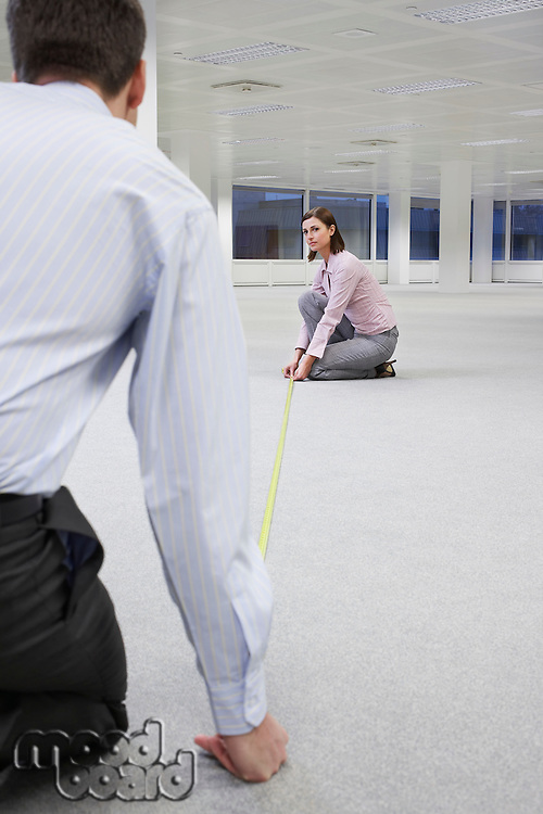Two office workers measuring floor in empty office space back view