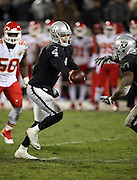 Oakland Raiders quarterback Derek Carr (4) hands off the ball on a running play during the NFL week 12 regular season football game against the Kansas City Chiefs on Thursday, Nov. 20, 2014 in Oakland, Calif. The Raiders won their first game of the season 24-20. ©Paul Anthony Spinelli