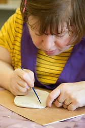 Day Service user concentrating whilst imprinting a pattern on a piece of modeling clay,
