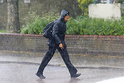 © Licensed to London News Pictures. 01/05/2020. London, UK. A man walks through a heavy downpour in north London as the coronavirus lockdown continues to slow the spread of COVID-19. Photo credit: Dinendra Haria/LNP