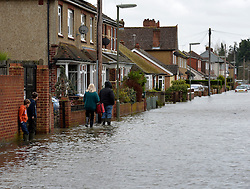 Local residents in South Avenue at Egham, Surrey attempt to get to their homes which have been badly affected by flooding, United Kingdom, Wednesday 12th February 2014. Picture by David Dyson / i-Images
