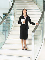 Confident Businesswomen holding folder standing on stairs hand on banister