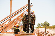 12 JUNE 2006 - SAN LUIS, AZ: Soldiers put a section of fence into place on the US/Mexico border. Fifty five members of the 116th Engineer Company, Combat Support Engineers, of the Utah Army National Guard are in San Luis, AZ, to build a fence and improve roads east of the San Luis Port of Entry on the US/Mexico border. The unit is the first of an estimated 6,000 US military personnel, almost all of them Army National Guard, who will be dispatched to the US/Mexico border by President Bush to help control immigration on the border. The Guardsmen will primarily build roads and fence and staff surveillance centers. They will not be engaged in first line law enforcement work.  Photo by Jack Kurtz