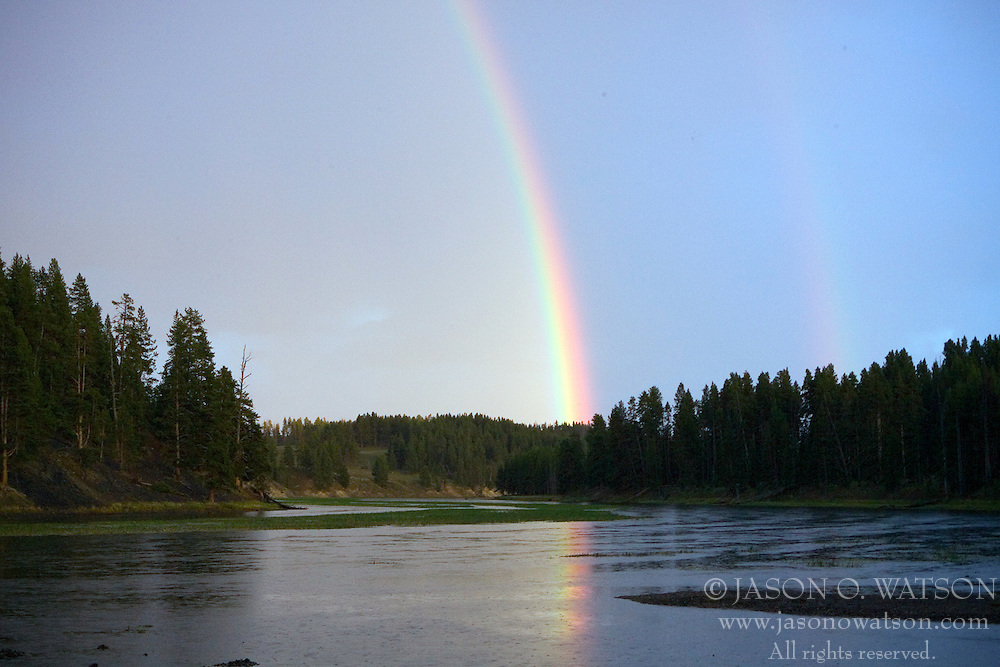 A rainbow forms at twilight over the Yellowstone River in Yellowstone National Park, Wyoming