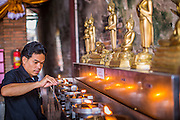 03 OCTOBER 2012 - AYUTTHAYA, THAILAND: A man lights oil lamps while praying at Wat Yai Chaimongkhon in Ayutthaya. Wat Yai Chaimongkhon is one of the most important temple's in Ayutthaya and was built in 1357. Ayutthaya is the former imperial capital of what was then Siam, now Thailand. Founded around 1350, Ayutthaya became the second capital of Siam after Sukhothai. Ayutthaya's location between China, India and the Malay Archipelago made Ayutthaya the trading capital of the rgion. By 1700 Ayutthaya was the largest city in the world with a total of 1 million inhabitants. The Ayutthaya empire and city were defeated by Burmese forces in April, 1767 when the city was sacked and its art treasures, libraries and archives were destroyed. All that remains in Ayutthaya now are ruins of former imperial temples and palaces because those were the only stone buildings of the time. Ayutthaya is less than 100 miles from Bangkok and is a popular day trip destination for Thai and foreign tourists.  PHOTO BY JACK KURTZ