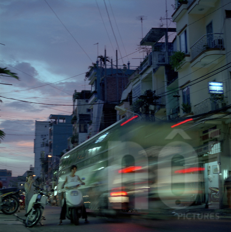a woman avoids being hit by a bus  at dusk, in the Backpackers area in Ho Chi Minh city, Vietnam.