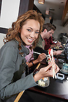 Young people eating sushi with chopsticks in restaurant
