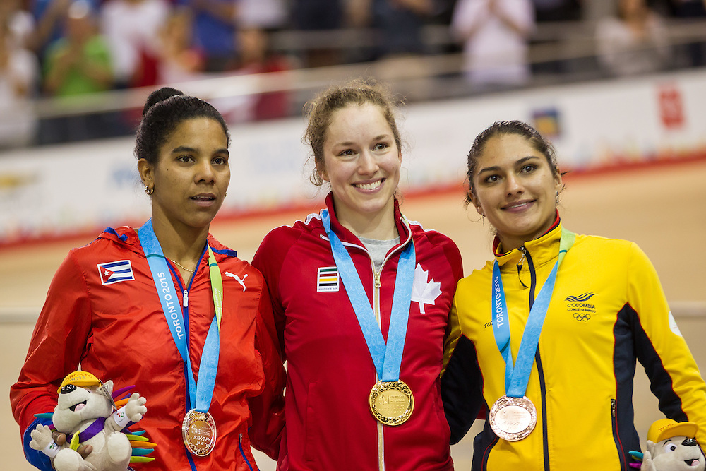 Gold medalist Monique Sullivan (C) of Canada is joined by Silver medalist  Lisandra Guerra (L) of Cuba and bronze medalist Juliana Gaviria Rendon during the medal ceremony for the women's cycling keirin finals at the 2015 Pan American Games in Toronto, Canada, July 17,  2015.  AFP PHOTO/GEOFF ROBINS